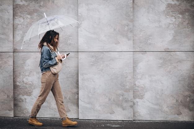 Joven mujer caminando bajo la lluvia con paraguas