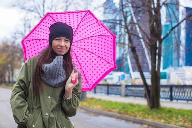 Joven mujer caminando con paraguas en otoño día lluvioso