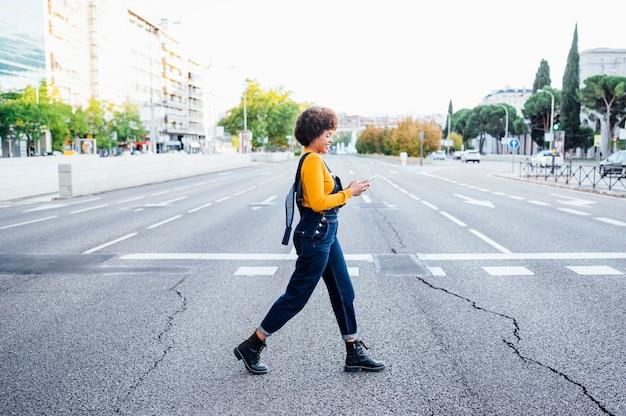 Joven mujer caminando por paso de cebra