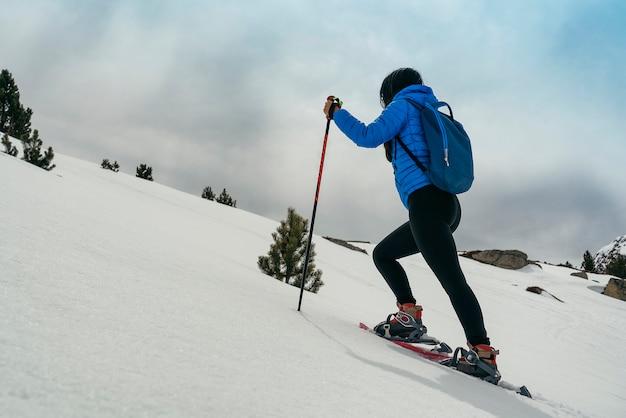 Joven mujer caminando con raquetas de nieve en alta montaña