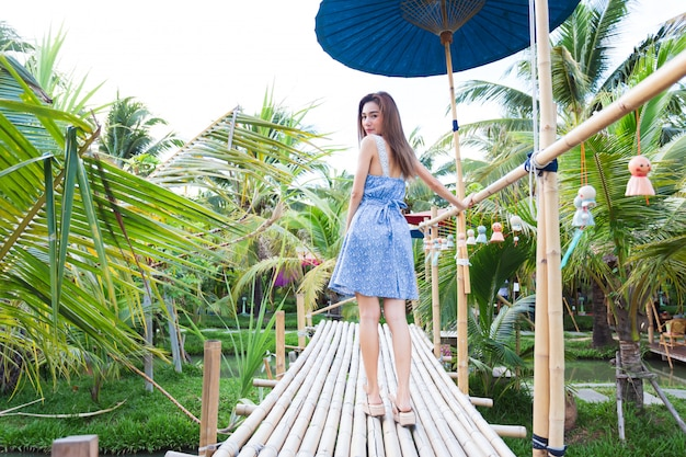 Joven mujer caminando sobre el puente de bambú
