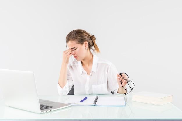 Joven mujer cansada delante de una computadora portátil en el escritorio de oficina, aislado sobre fondo blanco.