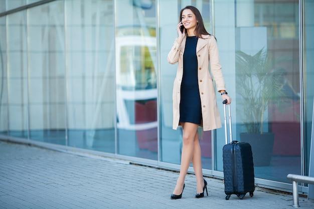 Joven mujer casual va al aeropuerto en la ventana con maleta esperando avión