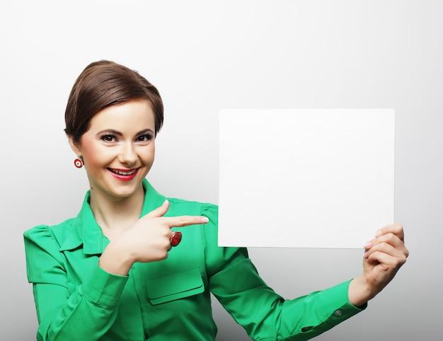 Joven mujer casual feliz con cartel en blanco