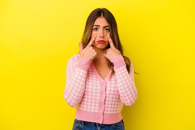 Joven mujer caucásica aislada en amarillo llorando, infeliz con algo, concepto de agonía y confusión.