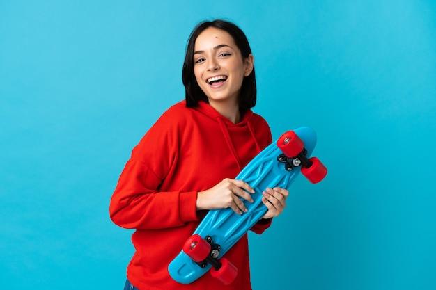 Joven mujer caucásica aislada en azul con un patín con expresión feliz