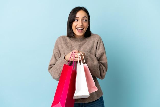 Joven mujer caucásica aislada en azul sosteniendo bolsas de compras y sorprendido