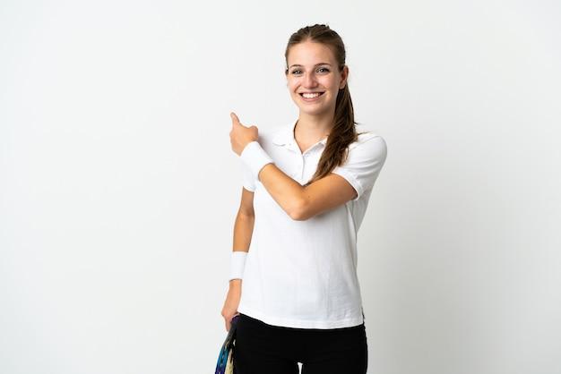 Joven mujer caucásica aislada en blanco jugando al tenis y apuntando hacia el lateral