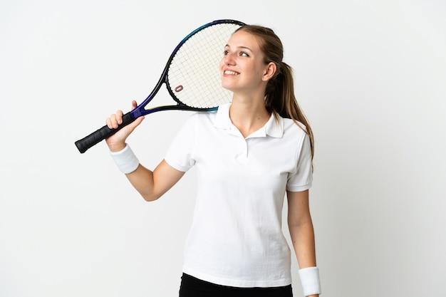 Joven mujer caucásica aislada en blanco jugando al tenis y mirando hacia arriba