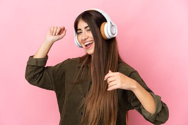 Joven mujer caucásica aislada escuchando música y bailando
