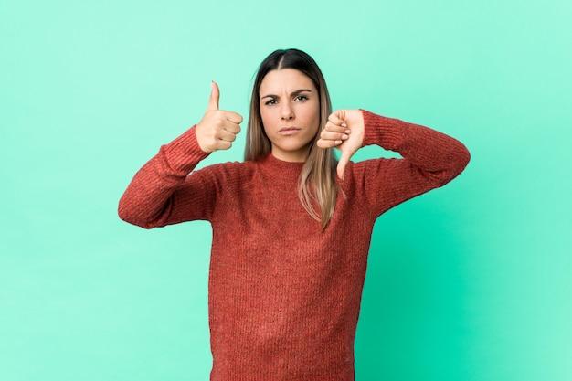 Joven mujer caucásica aislada mostrando los pulgares hacia arriba y hacia abajo, difícil elegir el concepto