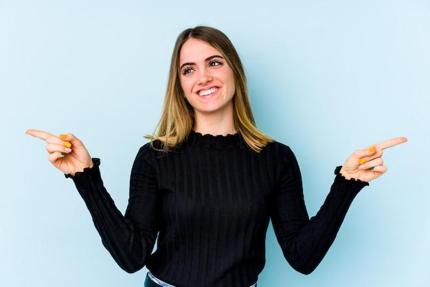 Joven mujer caucásica aislada en la pared azul apuntando a diferentes espacios de copia, eligiendo uno de ellos, mostrando con el dedo.