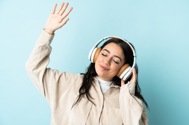 Joven mujer caucásica aislada en la pared azul escuchando música y bailando