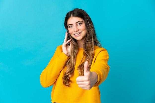 Joven mujer caucásica aislada en la pared azul manteniendo una conversación con el móvil mientras hace los pulgares para arriba