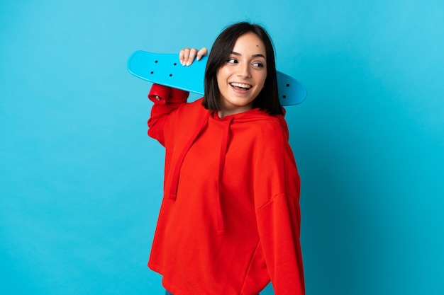 Joven mujer caucásica aislada en la pared azul con un patín con expresión feliz