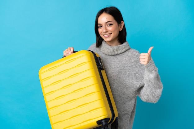 Joven mujer caucásica aislada en la pared azul en vacaciones con maleta de viaje y con el pulgar hacia arriba