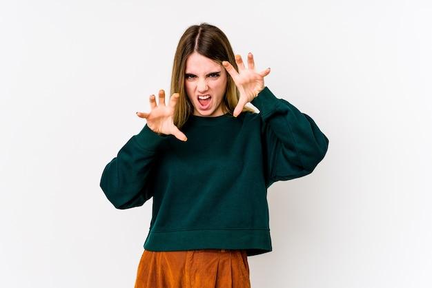 Joven mujer caucásica aislada en la pared blanca mostrando garras imitando un gato, gesto agresivo.