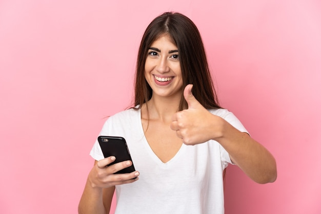Joven mujer caucásica aislada en la pared rosa con teléfono móvil mientras hace los pulgares para arriba
