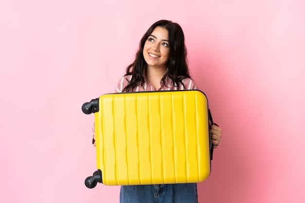Joven mujer caucásica aislada en la pared rosa en vacaciones con maleta de viaje