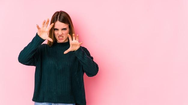 Joven mujer caucásica aislada en la pared rosada mostrando garras imitando un gato, gesto agresivo.