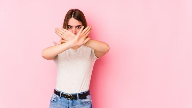 Joven mujer caucásica aislada en rosa haciendo un gesto de negación