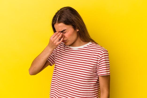 Joven mujer caucásica aislada sobre fondo amarillo con dolor de cabeza, tocando la parte delantera de la cara.