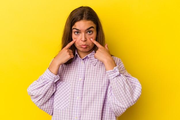 Joven mujer caucásica aislada sobre fondo amarillo llorando, infeliz con algo, concepto de agonía y confusión.