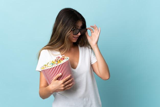 Joven mujer caucásica aislada sobre fondo azul con gafas 3d y sosteniendo un gran balde de palomitas de maíz