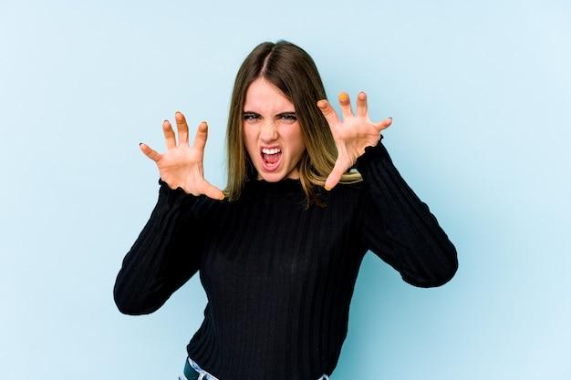 Joven mujer caucásica aislada sobre fondo azul mostrando garras imitando un gato, gesto agresivo.