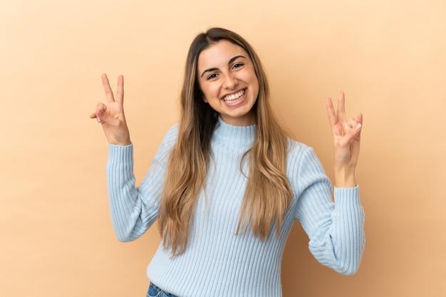 Joven mujer caucásica aislada sobre fondo beige mostrando el signo de la victoria con ambas manos