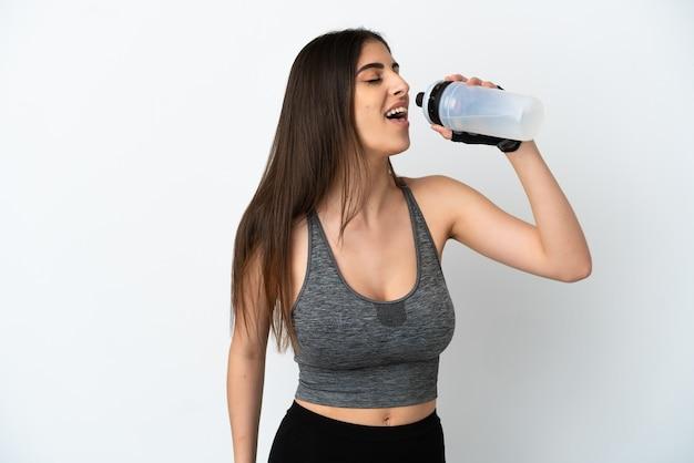 Joven mujer caucásica aislada sobre fondo blanco con botella de agua deportiva