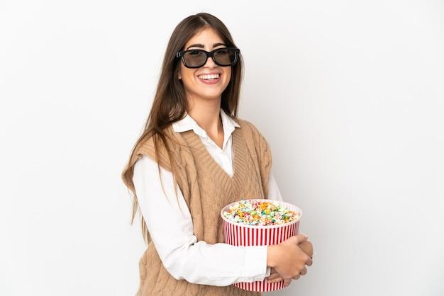 Joven mujer caucásica aislada sobre fondo blanco con gafas 3d y sosteniendo un gran balde de palomitas de maíz