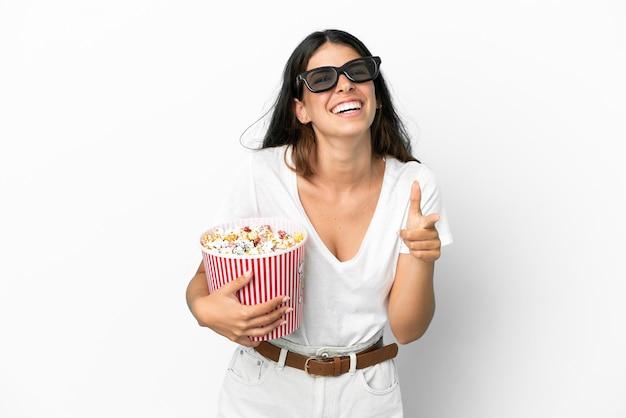 Joven mujer caucásica aislada sobre fondo blanco con gafas 3d y sosteniendo un gran cubo de palomitas de maíz mientras apunta hacia el frente