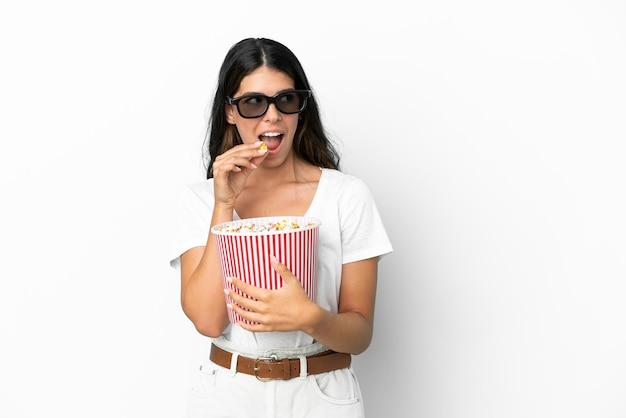 Joven mujer caucásica aislada sobre fondo blanco con gafas 3d y sosteniendo un gran cubo de palomitas de maíz mientras mira de lado
