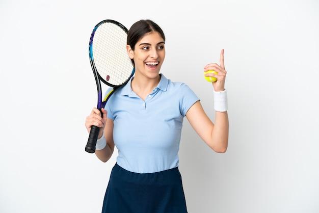 Joven mujer caucásica aislada sobre fondo blanco jugando al tenis y apuntando hacia arriba