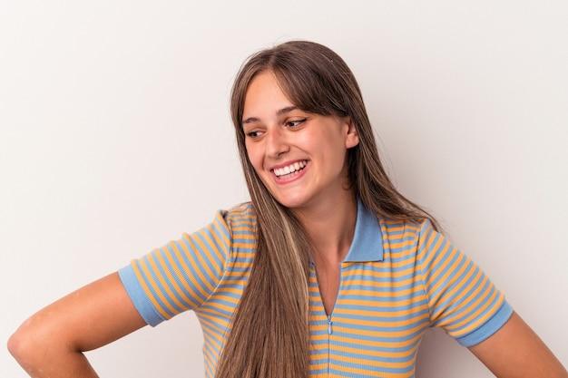 Joven mujer caucásica aislada sobre fondo blanco se ríe alegremente y se divierte manteniendo las manos sobre el estómago.