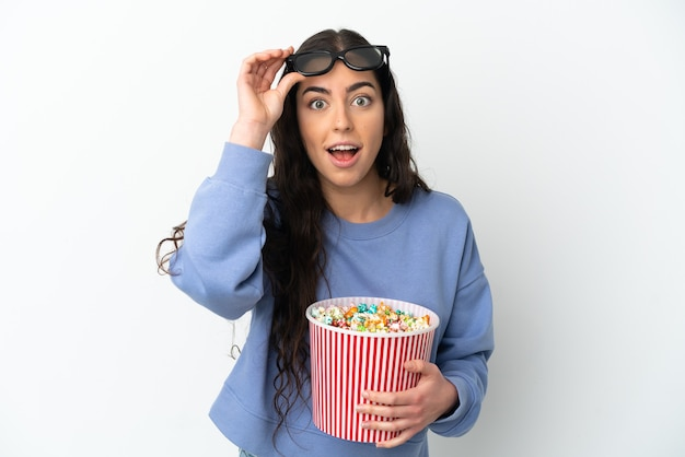 Joven mujer caucásica aislada sobre fondo blanco sorprendido con gafas 3d y sosteniendo un gran cubo de palomitas de maíz