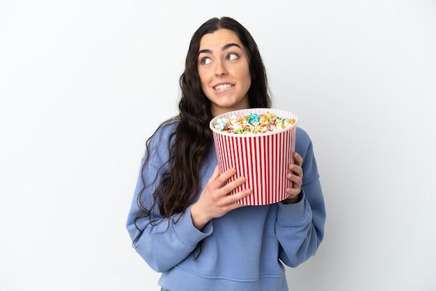 Joven mujer caucásica aislada sobre fondo blanco sosteniendo un gran balde de palomitas de maíz