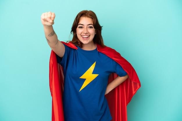 Joven mujer caucásica aislada sobre fondo blanco en traje de superhéroe con gesto orgulloso