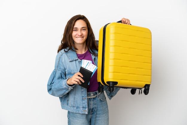 Joven mujer caucásica aislada sobre fondo blanco en vacaciones con maleta y pasaporte
