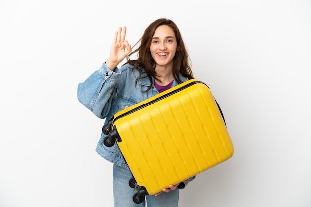 Joven mujer caucásica aislada sobre fondo blanco en vacaciones con maleta de viaje y haciendo el signo de ok