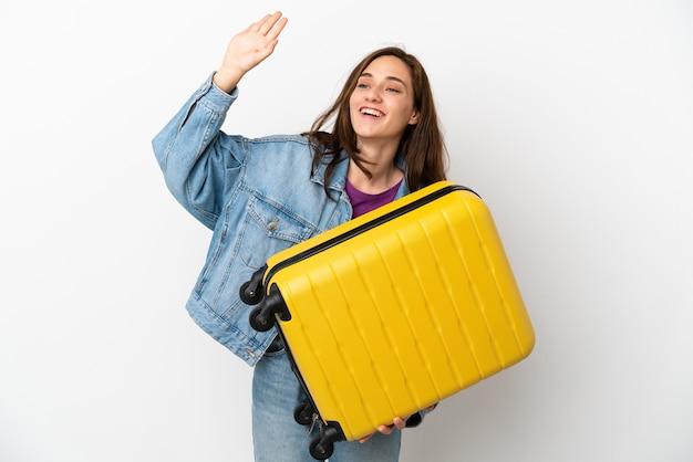 Joven mujer caucásica aislada sobre fondo blanco en vacaciones con maleta de viaje y saludando