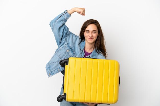 Joven mujer caucásica aislada sobre fondo blanco en vacaciones con maleta de viaje