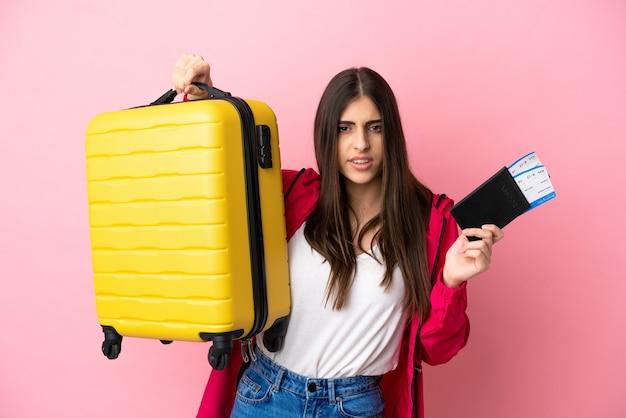 Joven mujer caucásica aislada sobre fondo rosa infeliz en vacaciones con maleta y pasaporte