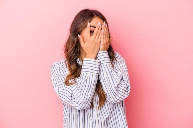 Joven mujer caucásica aislada sobre fondo rosa parpadea a través de los dedos asustada y nerviosa.