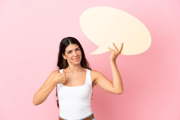 Joven mujer caucásica aislada sobre fondo rosa sosteniendo un bocadillo vacío con el pulgar hacia arriba