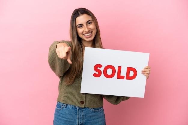 Joven mujer caucásica aislada sobre fondo rosa sosteniendo un cartel con el texto vendido y apuntando hacia el frente