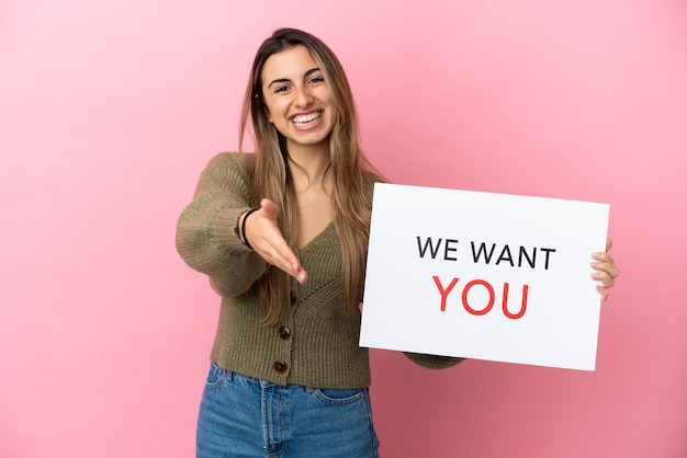 Joven mujer caucásica aislada sobre fondo rosa sosteniendo we want you board haciendo un trato