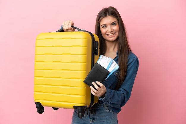 Joven mujer caucásica aislada sobre fondo rosa en vacaciones con maleta y pasaporte