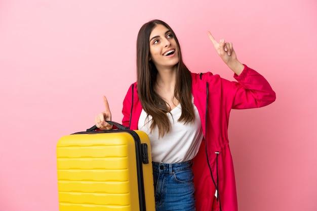 Joven mujer caucásica aislada sobre fondo rosa en vacaciones con maleta de viaje y apuntando hacia arriba